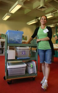 Photo of teacher with science kits and storage bins from Kennedy Library.