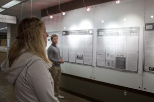 A blond woman stands in the foreground, examining the white wall of the gallery, which is lined with black-and-white research project proposal posters. A man in the background, standing beside the wall, looks at the camera.
