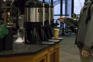 Three coffee pots sit on a counter; a man in a rain jacket fills a paper cup at the farthest coffee pot. We only see his arms and torso.