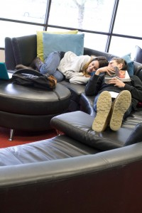 A man and woman nap next to each other on a half-circle leather couch. They are surrounded by backpacks, books, laptops and other school supplies.