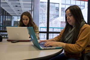 Two women sit at a table, working on laptops. They wear scarves and jackets. Behind them, we see out a window that it is gray and damp outside.