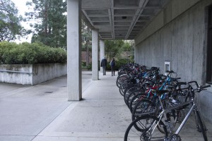 A row of bike racks, maybe 50 yards, crowded with bikes underneath a concrete overhang in front of the library.