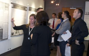 A blonde woman in black raises a hand to gesture as she explains her project to another woman. Behind them, at least six students in formalwear look at project posters on the wall.