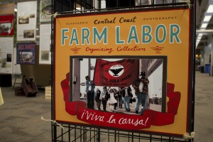 "A photo of an exhibit poster that says ""Farm Labor"" with a photo of farm laborers uniting."