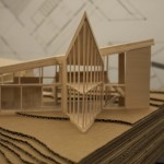 A wooden model of a building with upward sloping roofs that come to a triangular point.