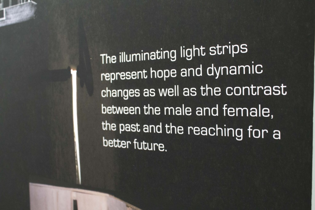 "A black piece of paper reads, ""The illuminating light strips represent hope and dynamic changes as well as the contrast between the male and female in the past and the reaching for a better future."""
