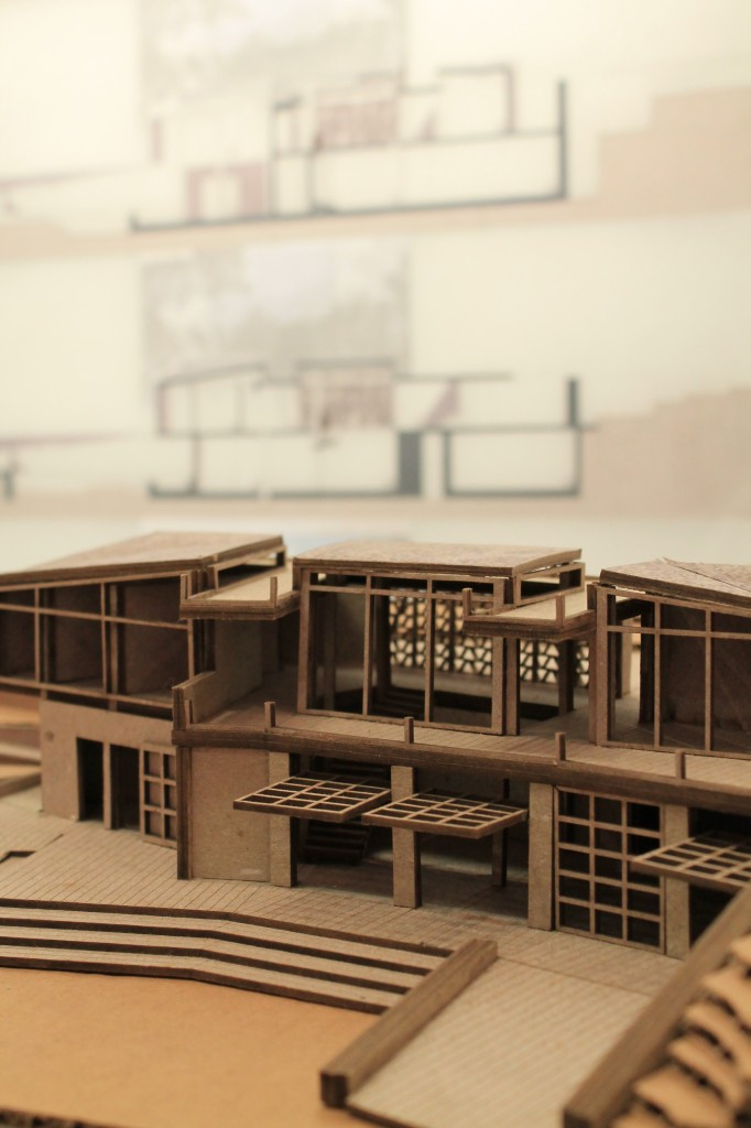 A cardboard model of a visitor's center with glass doors that swing upward to open.
