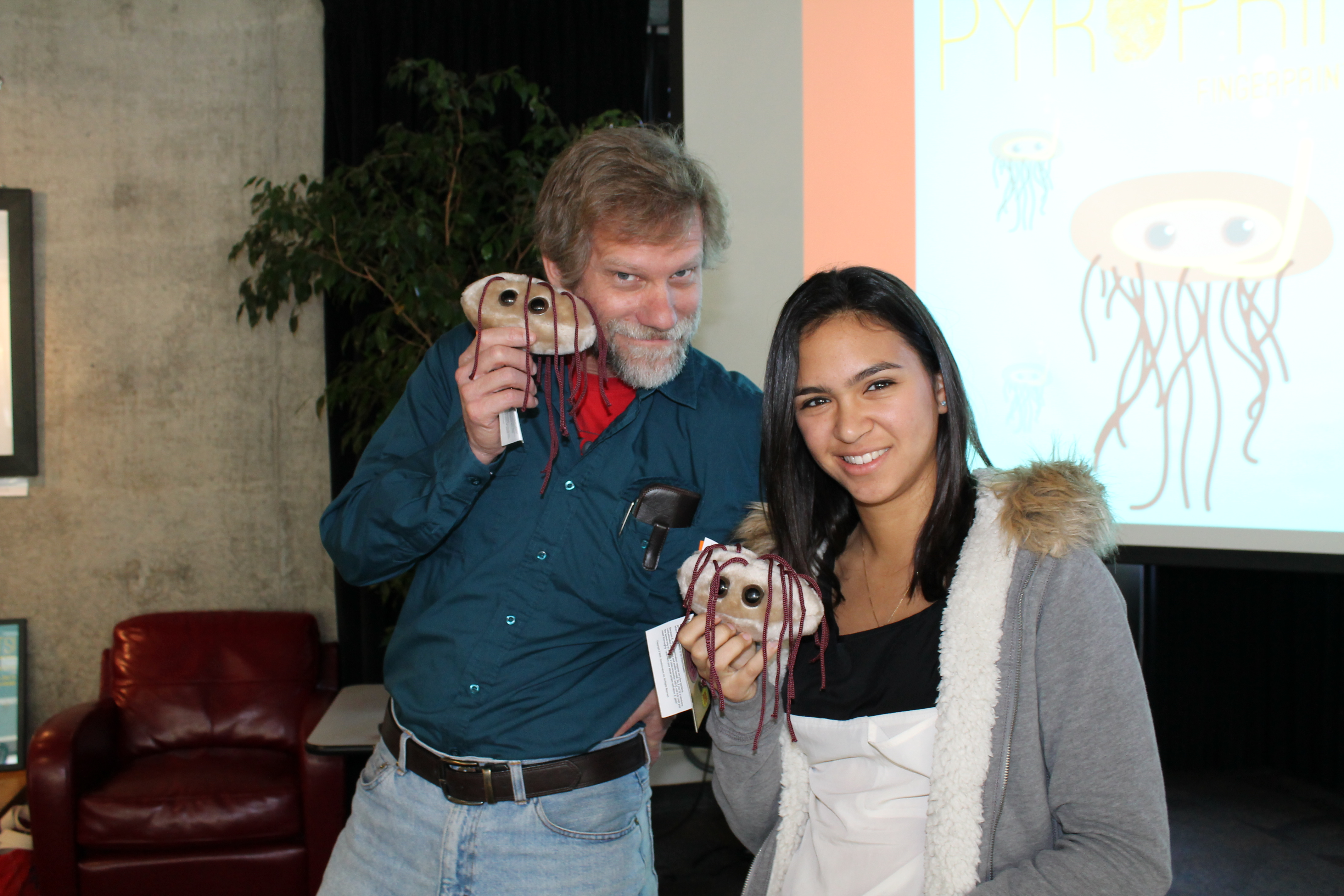 A bearded man and a young woman stand next to each other, smiling and holding small stuffed animal models of E. coli, which are fuzzy, oval-shaped and have two big eyes and little tentacles.