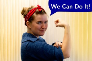 "A woman in a red bandana and blue shirt poses arm raised flexing her bicep and rolling up her sleeve like the iconic Rosie the Riveter poster. A blue speech bubble above her says ""We Can Do It!"""