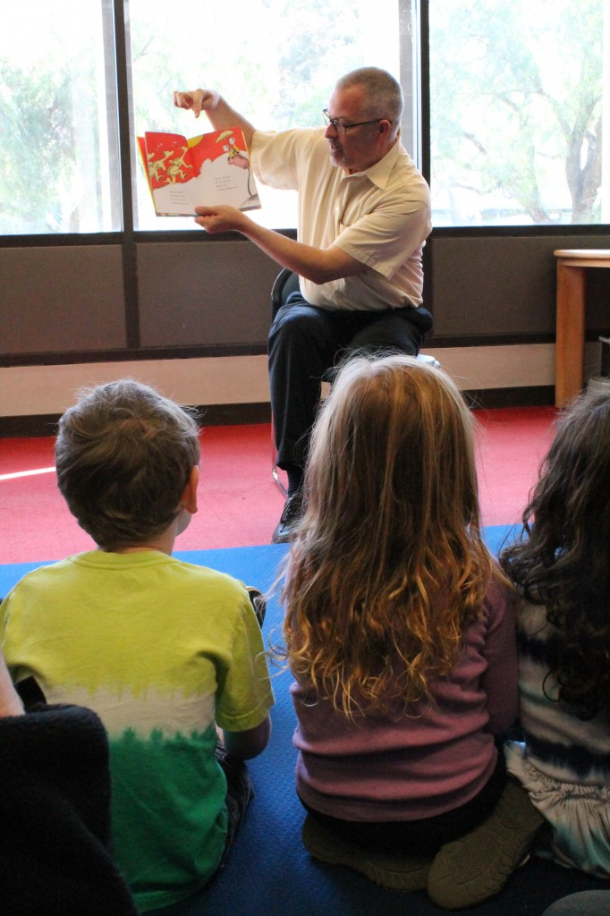 A man in glasses and a yellow shirt holds up One Fish, Two Fish, Red Fish, Blue Fish and points to the illustration. In front of him sit several young children.