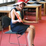 A woman in a blue dress and red and white striped Cat in the Hat hat sits on a chair reading Green Eggs and Ham with animated gestures.