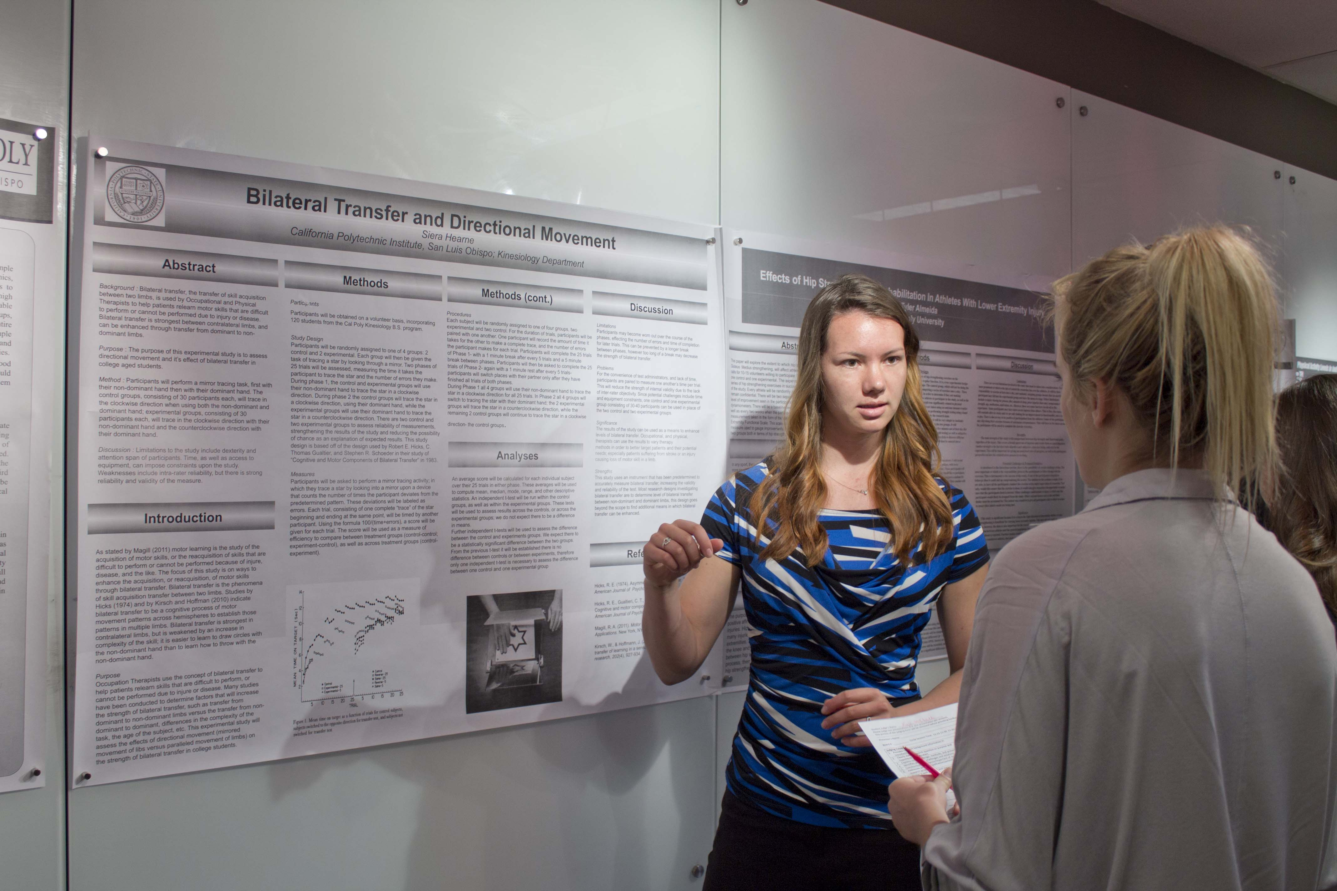 A woman with long hair and a blue, black and white top stands in front of a poster proposing a kinesiology research project. She is talking to a blonde woman standing in the foreground with her back to the camera.