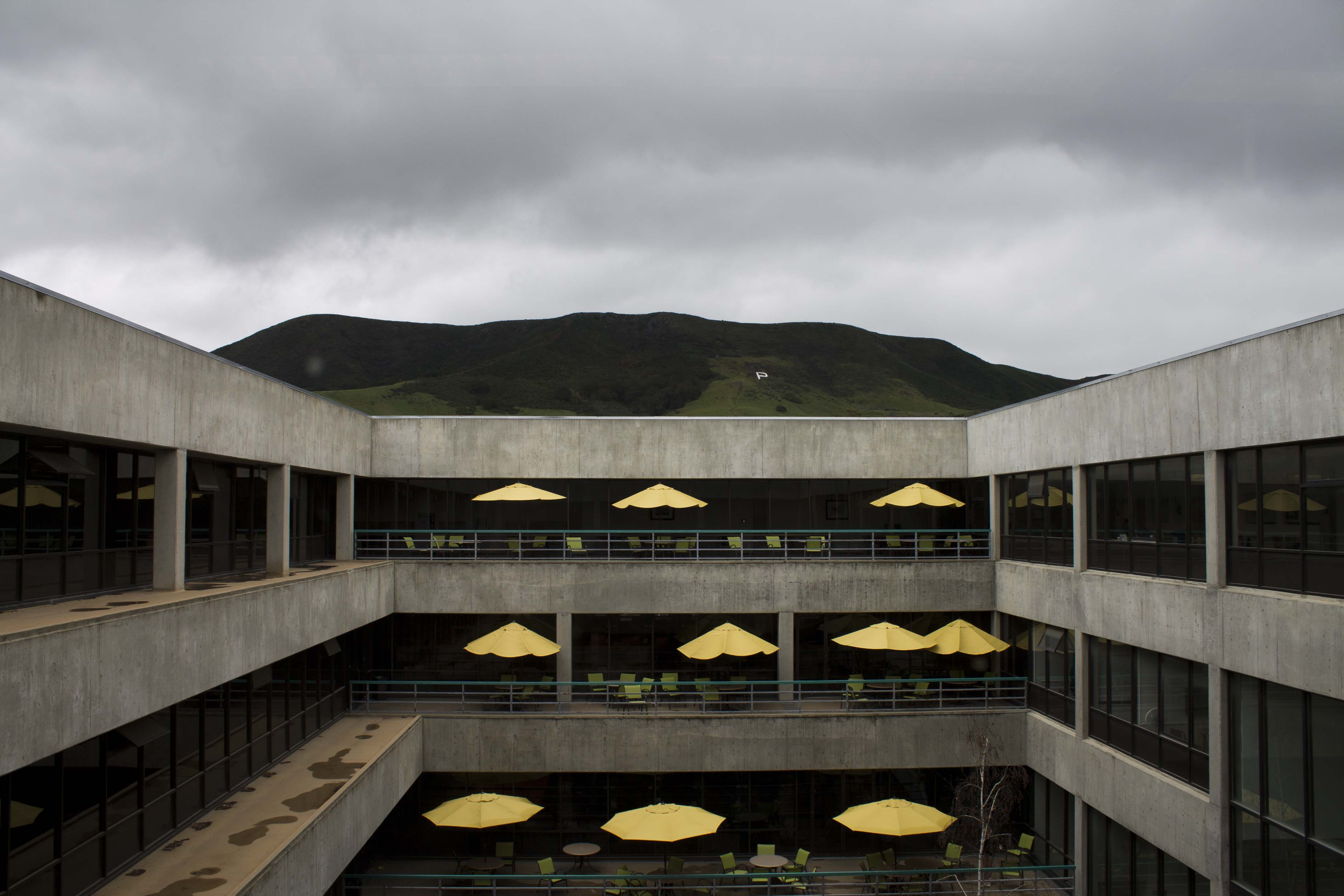 A photo from the 5th floor of Kennedy Library. We are looking out onto several stories of the cement and glass building. The balconies are decorated with tables with yellow umbrellas. In the background, there are gray rainclouds over a green mountain with a white letter P painted on it.
