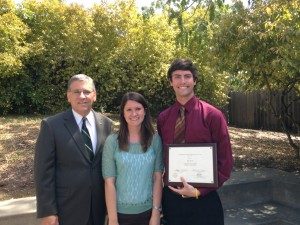 A man in a suit and glasses stands next to a young woman in turquoise and a young man in a burgundy button up and tie. The young man holds a plaque for Outstanding Student Employee of the Year. They are outside and it is sunny.