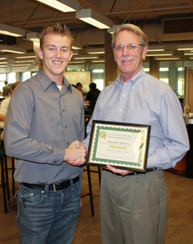 Ryan Cloney presents Library Dean Michael Miller with the Best Study Spot award.