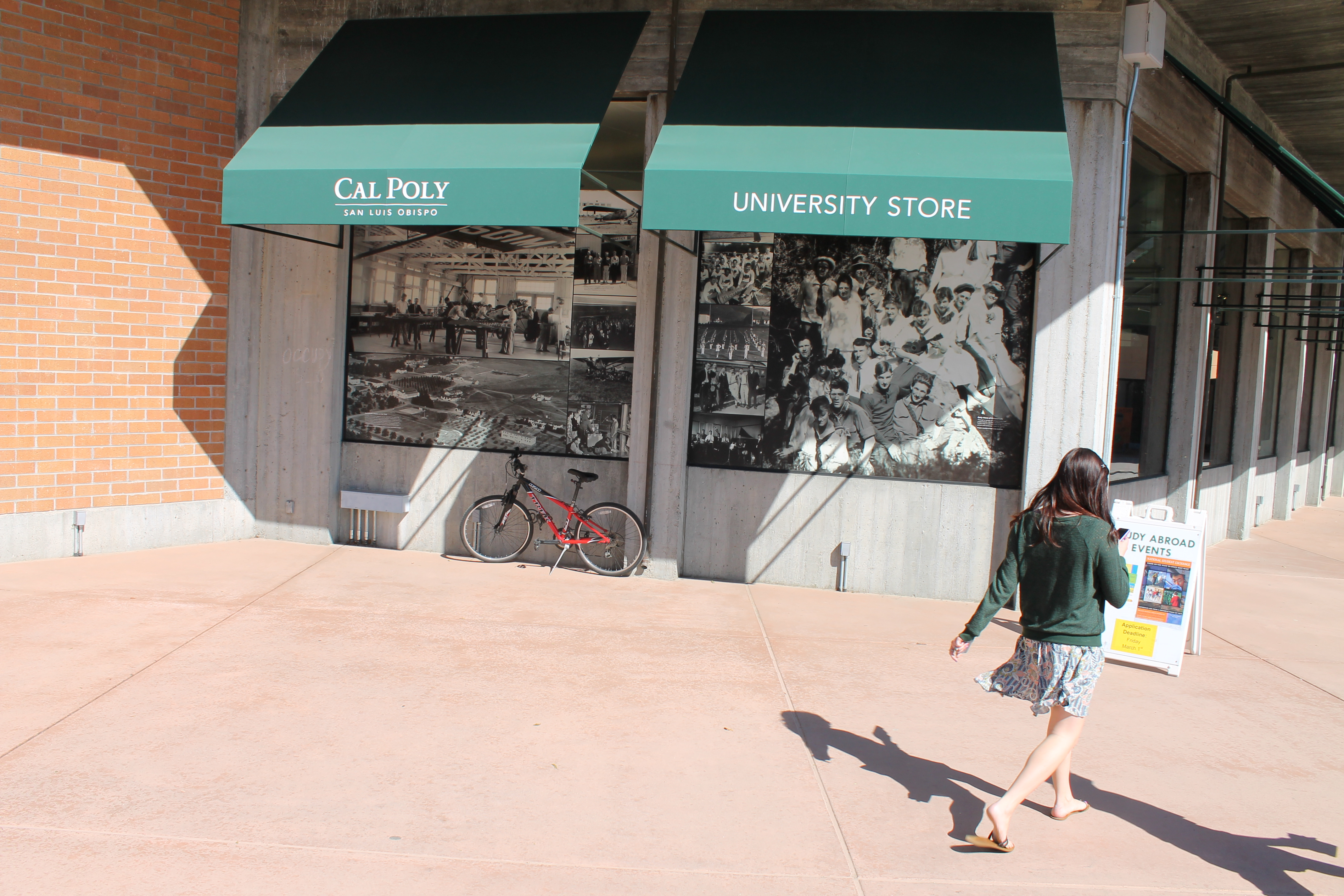"A photo of two windows, decorated with black and white photos of student groups. The green awnings above them say ""Cal Poly"" and ""University Store."" A women in a green sweater is walking by the photos."