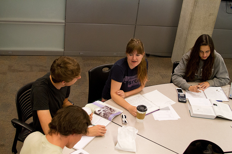 A photo of students sitting at a table, with books and papers laid out before them. They are studying.