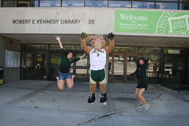 A photo of the Cal Poly mascot, Musty, jumping in the air with two students in front of Kennedy Library.