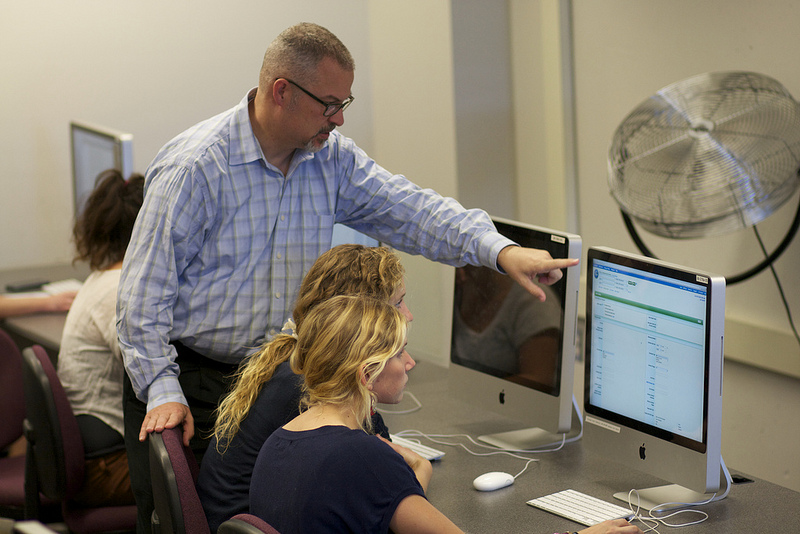 Business librarian Mark Bieraugel works with two students on a computer.