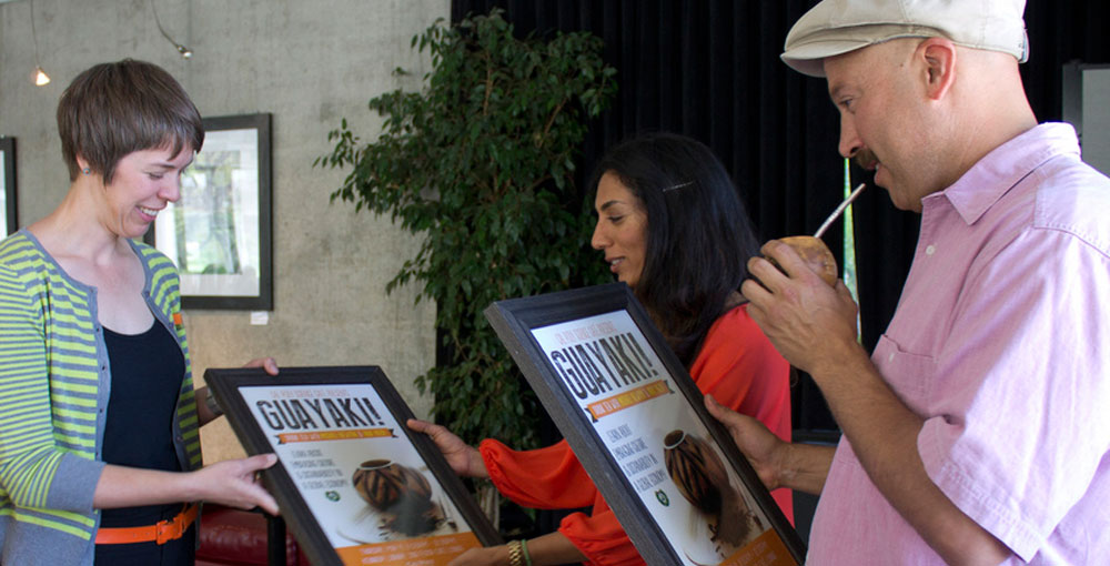 Photo of two presenters receiving a thank you poster at Cal Poly Science Cafe with Guayaki
