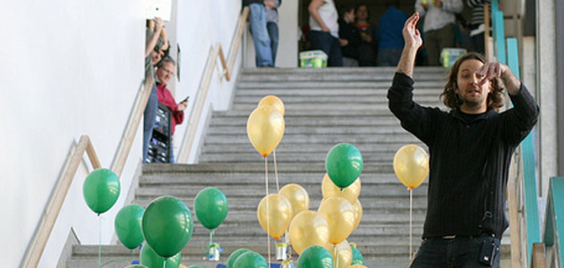Photo of Michael Newman in the stairs at Kennedy Library with green and gold balloons