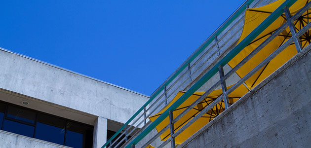 Photo of the a balcony, sky and yellow umbrellas at Robert E. Kennedy Library, Bldg. 35