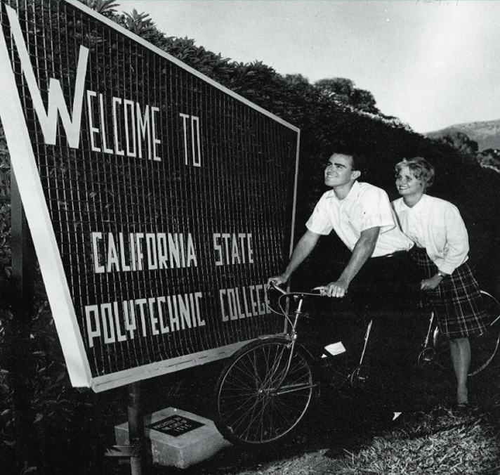Two students on a tandem bicycle near the Cal Poly entrance