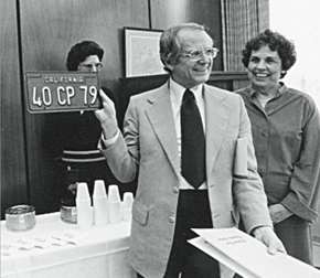 Dr. Kennedy holds up a commemorative license plate at his retirement celebration in 1979.