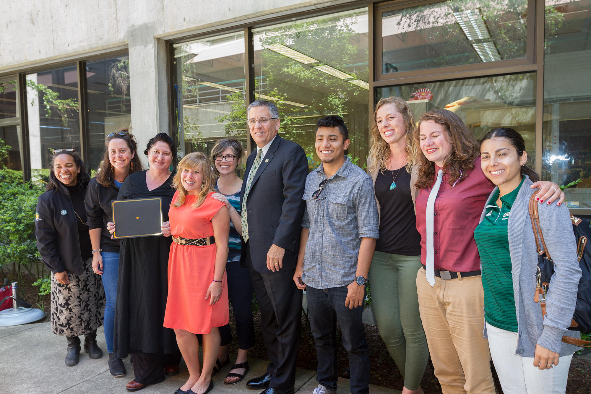 President Armstrong and the diversity award winners stood and smiled together in the library atrium.